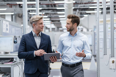 Two businessmen with tablet talking in a modern factory - DIGF07570