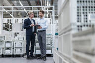 Two businessmen with tablet talking in a modern factory - DIGF07579