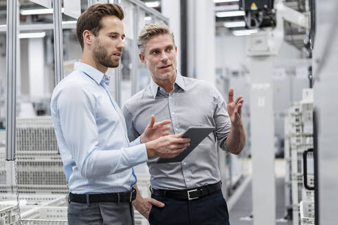 Two businessmen with tablet talking in a modern factory - DIGF07585