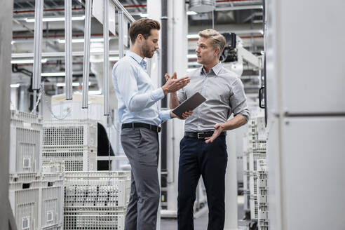 Two businessmen with tablet talking in a modern factory - DIGF07588