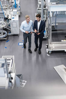 Two businessmen with clipboard talking in a factory - DIGF07591