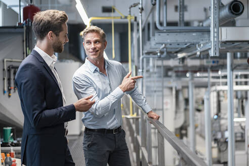Two businessmen talking in a modern factory - DIGF07594