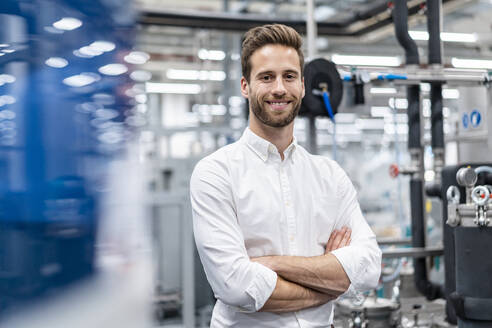 Portrait of a smiling businessman in a modern factory - DIGF07633