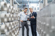 Two businessmen with tablet talking in a modern factory - DIGF07645