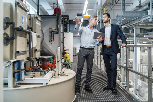 Two businessmen with tablet talking in a modern factory - DIGF07657