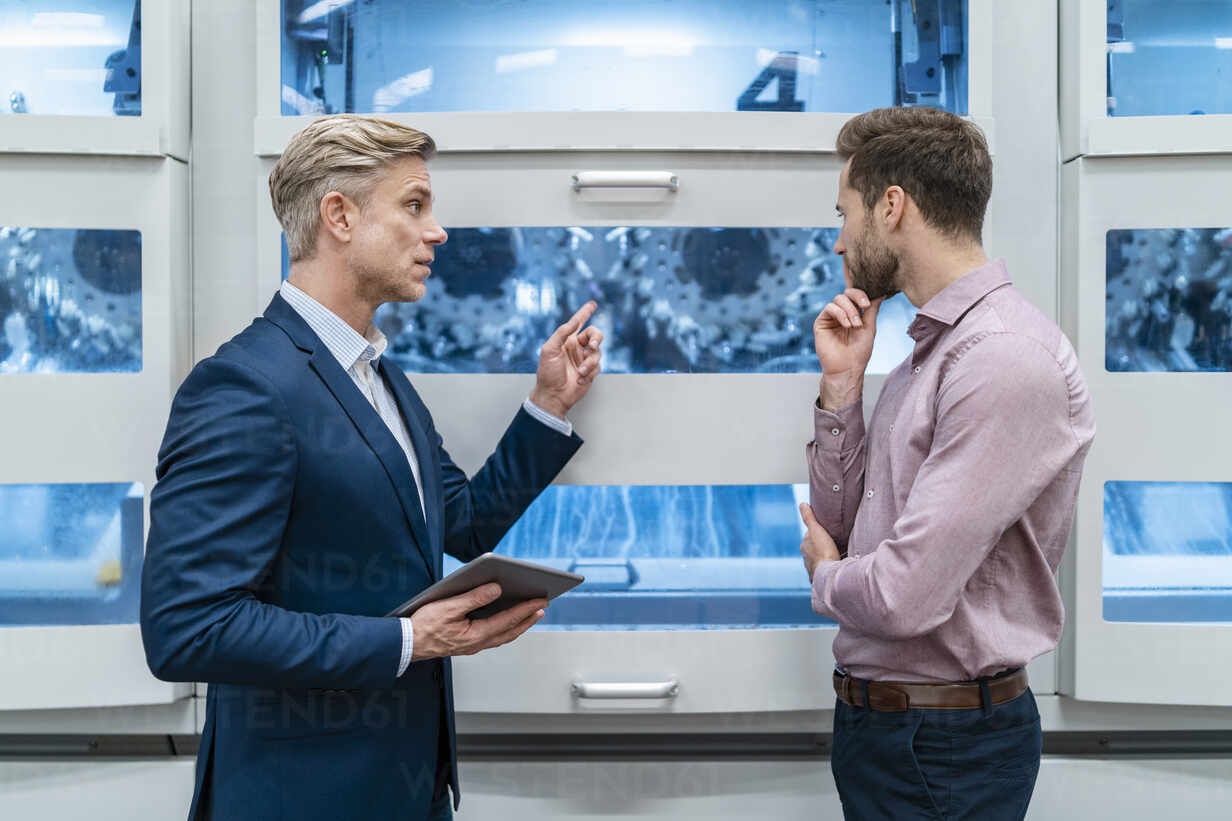 Two businessmen with tablet talking at machine in a modern factory - DIGF07681 - Daniel Ingold/Westend61