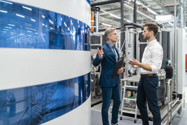 Two businessmen talking in a modern factory - DIGF07696