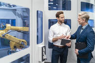 Two businessmen talking at robot in a modern factory - DIGF07699
