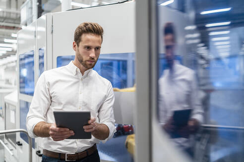 Businessman using tablet in a modern factory - DIGF07702
