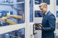 Businessman using tablet at a robot in a modern factory - DIGF07705