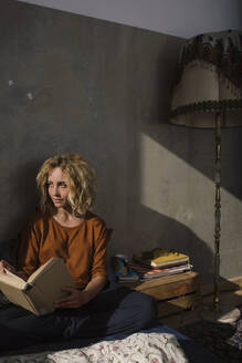 Blond student sitting on bed with a book looking at distance - GCF00264