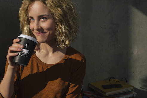 Portrait of smiling young woman drinking coffee to go at home - GCF00270