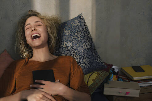 Portrait of laughing young woman lying on bed with E-book reader - GCF00279