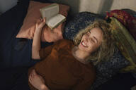 Portrait of laughing young woman with eyes closed lying on bed with a book - GCF00285