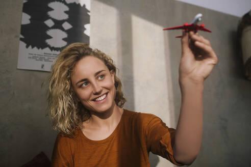 junge Frau mit Spielzeug-Flugzeug, Wohnung, Deutschland, Berlin, Studentin im WG-Zimmer - GCF00303