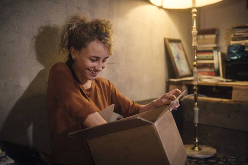 Smiling young woman unpacking parcel at home - GCF00312
