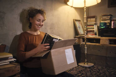 Smiling young woman unpacking parcel at home - GCF00315