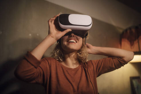 Laughing young woman putting on Virtual Reality Glasses at home - GCF00318