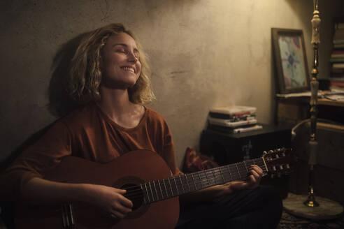 junge Frau mit Gitarre, Wohnung, Deutschland, Berlin, Studentin im WG-Zimmer - GCF00330