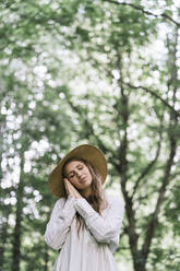 Young woman with hat enjoying the forest - AHSF00586