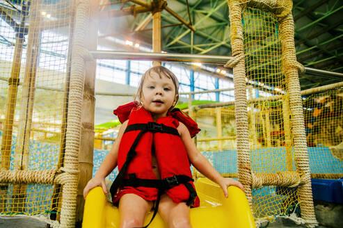 Caucasian girl riding slide at water park - BLEF10281
