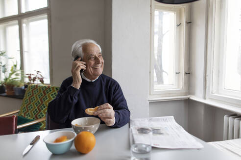 Smiling senior man on cell phone at home - GUSF02052