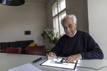 Portrait of smiling senior man using tablet with architectural plan - GUSF02064