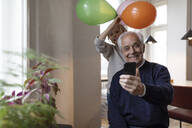 Happy grandfather and grandson taking a selfie with balloons at home - GUSF02085