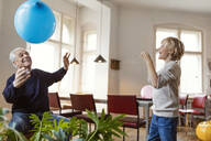 Happy grandfather and grandson playing with balloon at home - GUSF02088