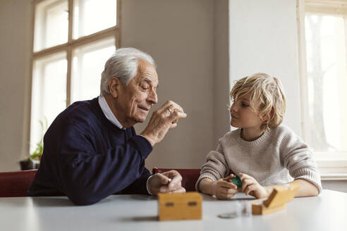 Watchmaker and his grandson examining watch together - GUSF02091