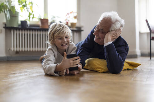 Grandfather and grandson lying on the floor at home using a smartphone - GUSF02100