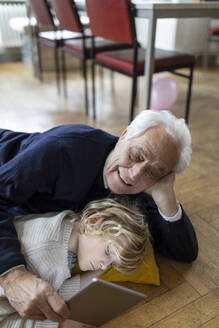Grandfather and grandson lying on the floor at home using a tablet - GUSF02103