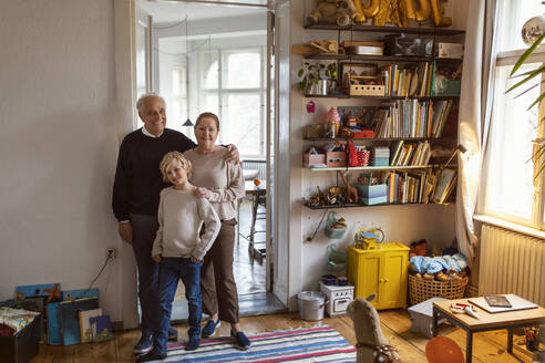 Portrait of happy grandparents with grandson at home - GUSF02118