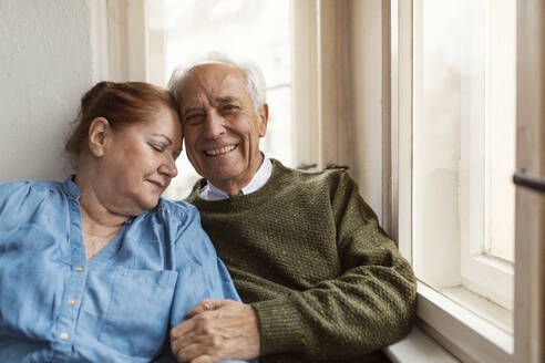 Portrait of happy senior couple at the window - GUSF02121
