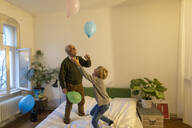 Happy grandfather and grandson playing with balloons on bed at home - GUSF02127
