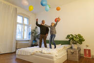 Happy grandfather and grandson playing with balloons on bed at home - GUSF02130