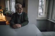 Smiling senior man sitting at table at home - GUSF02133