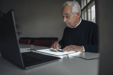 Senior man using tablet with architectural plan - GUSF02145