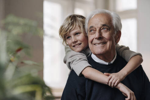 Happy grandson embracing grandfather at home - GUSF02166