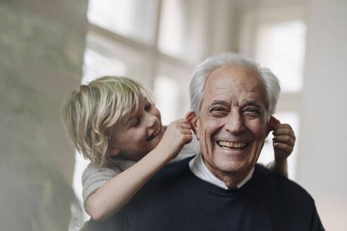 Happy grandson pulling grandfather's ears at home - GUSF02169