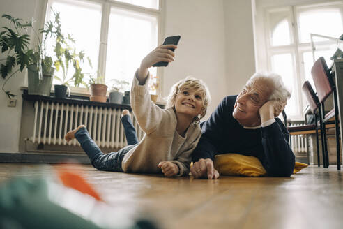 Grandfather and grandson lying on the floor at home taking a selfie - GUSF02181