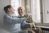 Happy senior couple with flower at home - GUSF02202