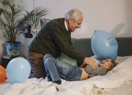 Happy grandfather playing with grandson on bed at home - GUSF02208