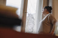 Serious senior woman looking out of window at home - GUSF02217