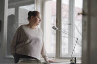Serious senior woman looking out of window at home - GUSF02235