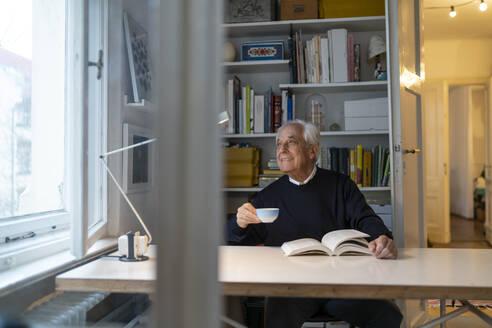 Senior man reading book at home - GUSF02238