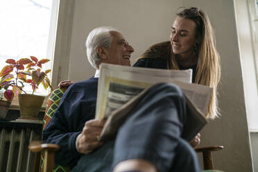 Happy young woman and senior man with newspaper at home - GUSF02244