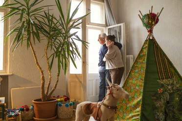 Senior couple standing in children's room looking out of window - GUSF02256