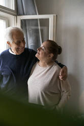 Happy senior couple at the window at home - GUSF02259