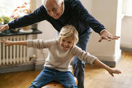 Happy grandfather and grandson playing with buck at home - GUSF02265
